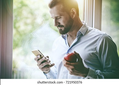 handsome businessman using smart phone and eating apple