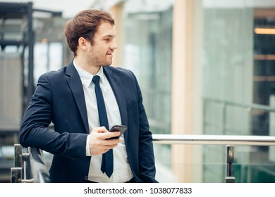 Handsome businessman using smartphone in the office