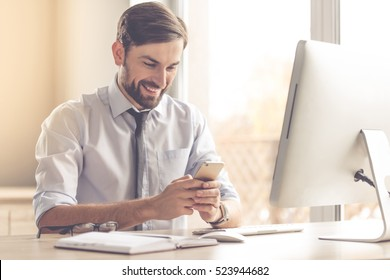 Handsome businessman is using a smartphone and smiling while working in office