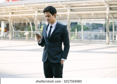 A handsome businessman using a smartphone. working by using smart phone in remote working concept. Business and information technology concept. standing street with city in the background
