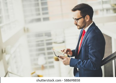 Handsome businessman using tablet in office