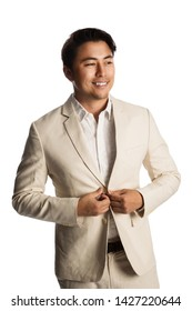 Handsome businessman wearing light colored suit, feeling calm and relaxed smiling. White background.