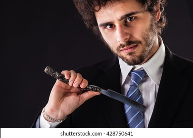 an handsome businessman wearing a suit and a tie holding a big cut-throat razor
