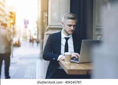 Handsome businessman wearing suit and using modern laptop outdoors, successful manager working in cafe during break and searching information in internet on his notebook computer