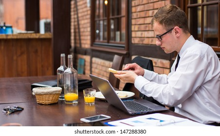 Handsome businessman work at the laptop in restaurant. Close-up.