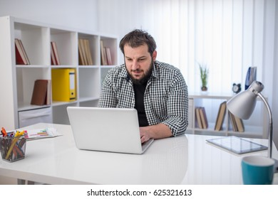 Handsome businessman working with laptop in firm office