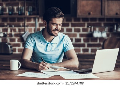Handsome Businessman Working with Laptop Home. Smiling Man Working and is Using Laptop while Making Notes on Paper. Freelance Worker. Happy Businessman Work Home.Paper Graphics, Cup of Coffee.