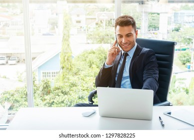 Handsome businessman working with mobile and laptop in office.