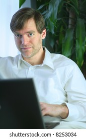 Handsome businessman working on laptop in casual attire.