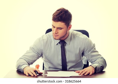 Handsome businessman writing a note in the office.