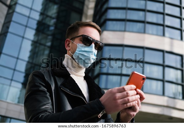 Handsome businessmanin with medical mask on the street  talking on the cellphone.  quarantine concept