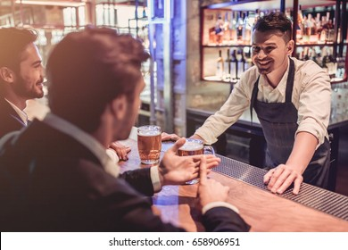 Handsome businessmen in bar are drinking beer and communicating with cheerful bartender.