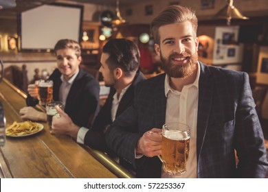 Handsome businessmen are drinking beer, talking and smiling while resting at the pub. Bearded guy is looking at camera