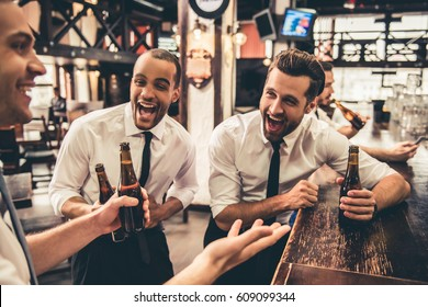 Handsome businessmen are drinking beer, talking and laughing while resting at the pub