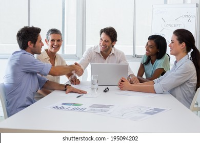 Handsome businessmen shaking each others hands after amazing presentation