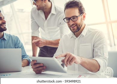 Handsome businessmen are using gadgets, talking and smiling while working in office