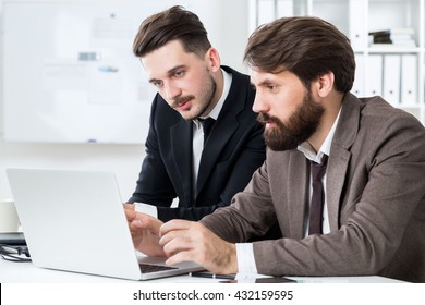 Handsome businesspeople with beards sitting at office desk and discussing business project on laptop