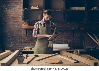 handsome cabinetmaker look at digital tablet  Stylish craftsman with brutal hairstyle and saved glasses work at his workplace.