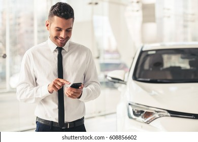 Handsome car dealership worker in suit is using a smart phone and smiling while standing near the car