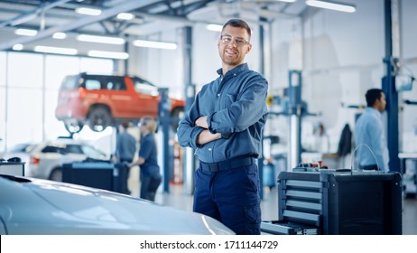 Handsome Car Mechanic is Posing in a Car Service. He Wears a Jeans Shirt and Safety Glasses. His Arms are Crossed. Specialist Looks at a Camera and Smiles.