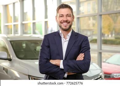 Handsome car salesman in dealership centre