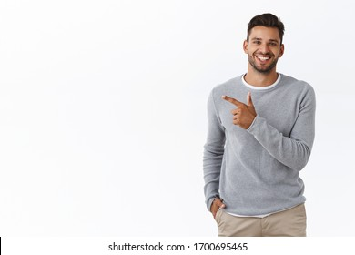 Handsome carefree bearded caucasian man in grey sweater, pointing left, discuss product, smiling as talking to you with friendly expression, showing around, introduce promo banner, white background
