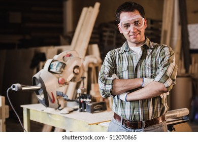 Handsome carpenter in protective glasses is looking at camera and smiling while standing near his wooden object in the workshop