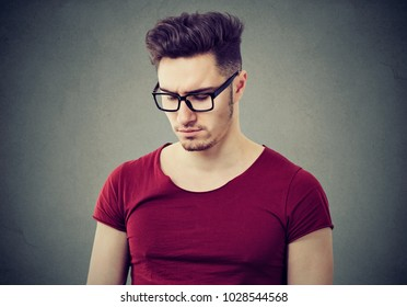 Handsome casual man in eyeglasses looking down with feeling of sadness standing on gray background.