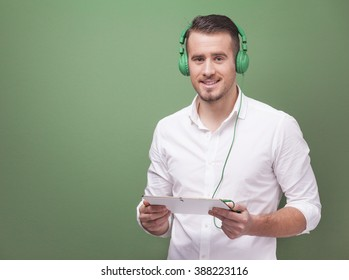 Handsome casual man listening to music with a digital tablet on green background