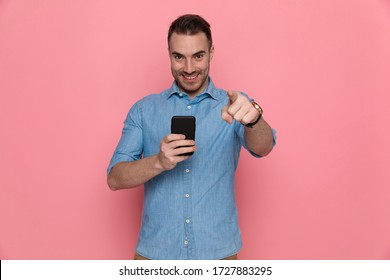 handsome casual man pointing forward, writing a message on his phone and smiling on pink studio background