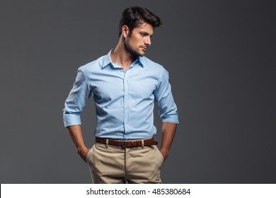 2a772103d Handsome casual man standing with arms in pockets isolated on a gray  background and looking away