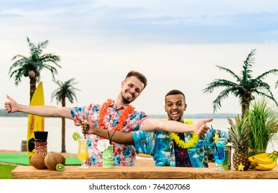 Handsome caucasian bartender and Latin American barman standing near the bar counter and thumbs up on the ocean. Concept of preparation, relaxing and fun