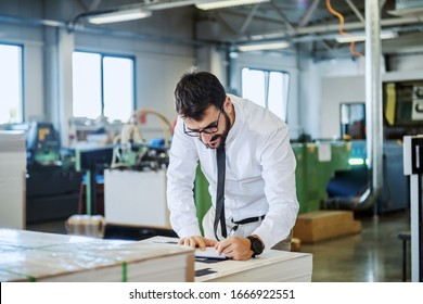 Handsome caucasian bearded supervisor with eyeglasses and in shirt and tie checking on quality of printed sheets while standing in printing shop.