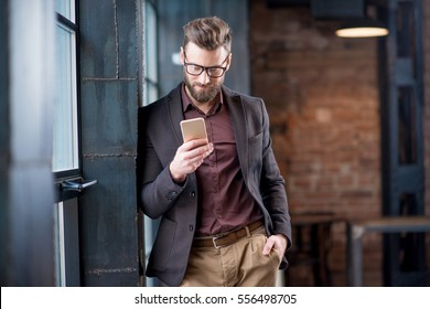 Handsome caucasian businessman dressed in the suit reading with his smart phone near the window in the loft interior studio