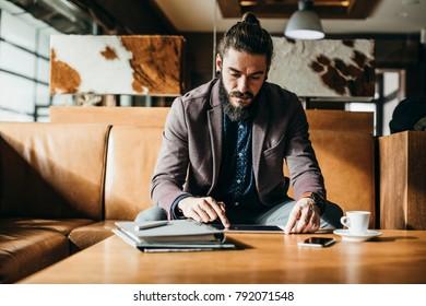 Handsome Caucasian businessman freelancer using tablet at hotel foyer.