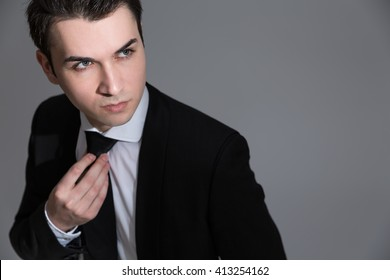 Handsome caucasian businessman looking away from the camera on light grey background