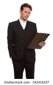 Handsome Caucasian businessman reading clipboard isolated against white background