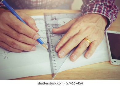 Handsome caucasian engineer work for architectural project.With a cup of coffee,tools,paper and white helmet on work table with a blueprints at home office.