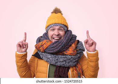 Handsome caucasian funny man in several hats and scarfs pointing with index finger up on pink background. Winter fashion.