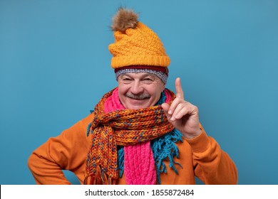 Handsome caucasian funny man in several hats and scarfs pointing up giving advice on blue background. Winter season concept.