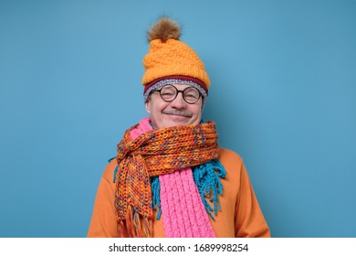 Handsome caucasian funny senior man in several hats and scarfs on blue background. Winter fashion.