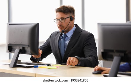 Handsome caucasian happy male operator wearing black suit white shirt and blue necktie sit smiling to camera and working receiving call by headphone microphone behind big monitor in office room.