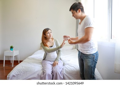 handsome caucasian husband giving medicine to his asian pregnant belly wife with love, but she doesn't want to eat with unhappy face.