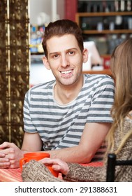 Handsome Caucasian male sitting at table with friend