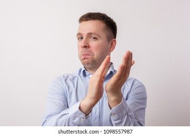 Handsome caucasian man applauding. He has funny emotion on his face