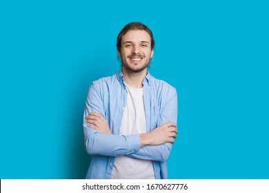 Handsome caucasian man with beard and long hair is posing with crossed hands on a blue background