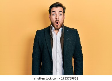 Handsome caucasian man with beard wearing elegant business jacket scared and amazed with open mouth for surprise, disbelief face