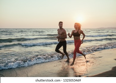 Handsome Caucasian man and beautiful woman running on sandy beach in sunset.