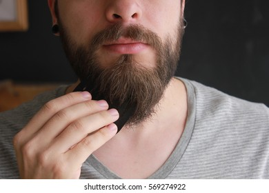 Handsome caucasian man close up comb his beard and mustache