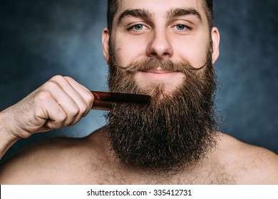 Handsome caucasian man close up with funny mustache comb beard and smile. Horizontal